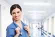 photo d'une jeune médecin souriante en bleu et tenant un sthetoscope autour du cou