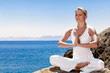 image d'uen femme faisant du yoga pour preserver sa sante au bord de la mer