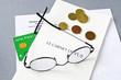 image avec une ordonnance, des lunnettes, de la monnaie, et une carte vitale pour assurance mutuelle santé