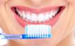 photo d'une jeune femme souriante montrant ses dents et tenant une brosse à dents bleue dans sa main droite