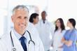 photo d'un medecin souriant derrière lequel il y a un groupe de jeune médecin qui discutent