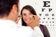Photo d'un opticien qu'on voit de dos tendant des lunettes pour une cliente souriante après avoir passer les tests de vues