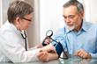 photo decrivant un jeune medecin pre,a,t la tension d'un patient ayant une assurance mutuelle santé