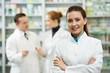 photo présentant une pharmacienne sans un premier plan et en arriere plan deux pharmacien en train de discuter devant le comptoir de médicaments