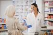 image d'une patiente et d'une pharmacienne tenant une poche à médicaments à sa cliente