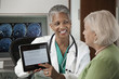 photo d'une médecin souriante montrant un dossier sur tablette à sa patiente