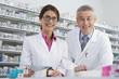 photo de deux pharmaciens souriants donnant les médicaments notés dans l'ordonnace au patient
