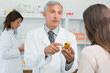 image d'un pharmacien conseillant une patiente sur le medicament qui tient dans la main
