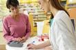 photo d'une pharmacienne expliquant à sa cliente qui se trouve en face d'elle les relations entre la caisse primaire d'assurance et les organismes de santé