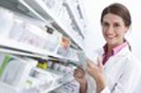 photo représentant une pharmacienne souriante lisant l'ordonnance et cherchant les médicaments