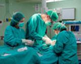 image d'un groupe de trois médecins effectuant une opération à un patient