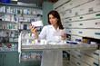 image d'une pharmacienne lisant l'ordonnance d'une patiente et regardant le médicament corespondant