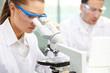 photo de deux médecins chercheurs dans un laboratoire où une médecin est en train de regarder à l'aide d'un microscope